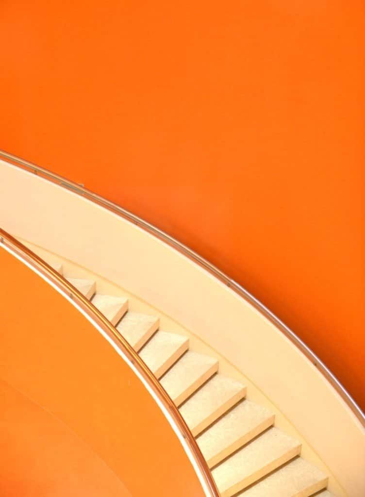 an orange background with light cream stairs.